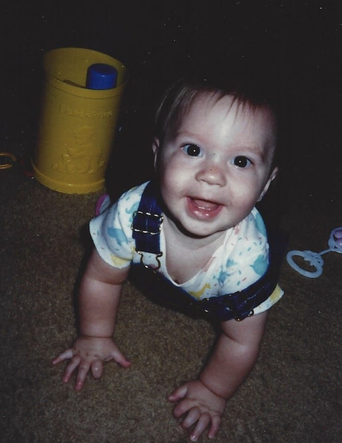 baby smiling at the camera while crawling on hands and knees