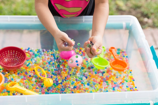 A child playing in a sensory bin full of waterbeads and play toys