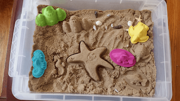 Sand sensory bin filled with sand toys for playing in the sand with