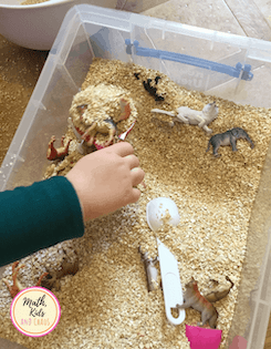 Child's hand playing in a sensory bin full of oats and toys