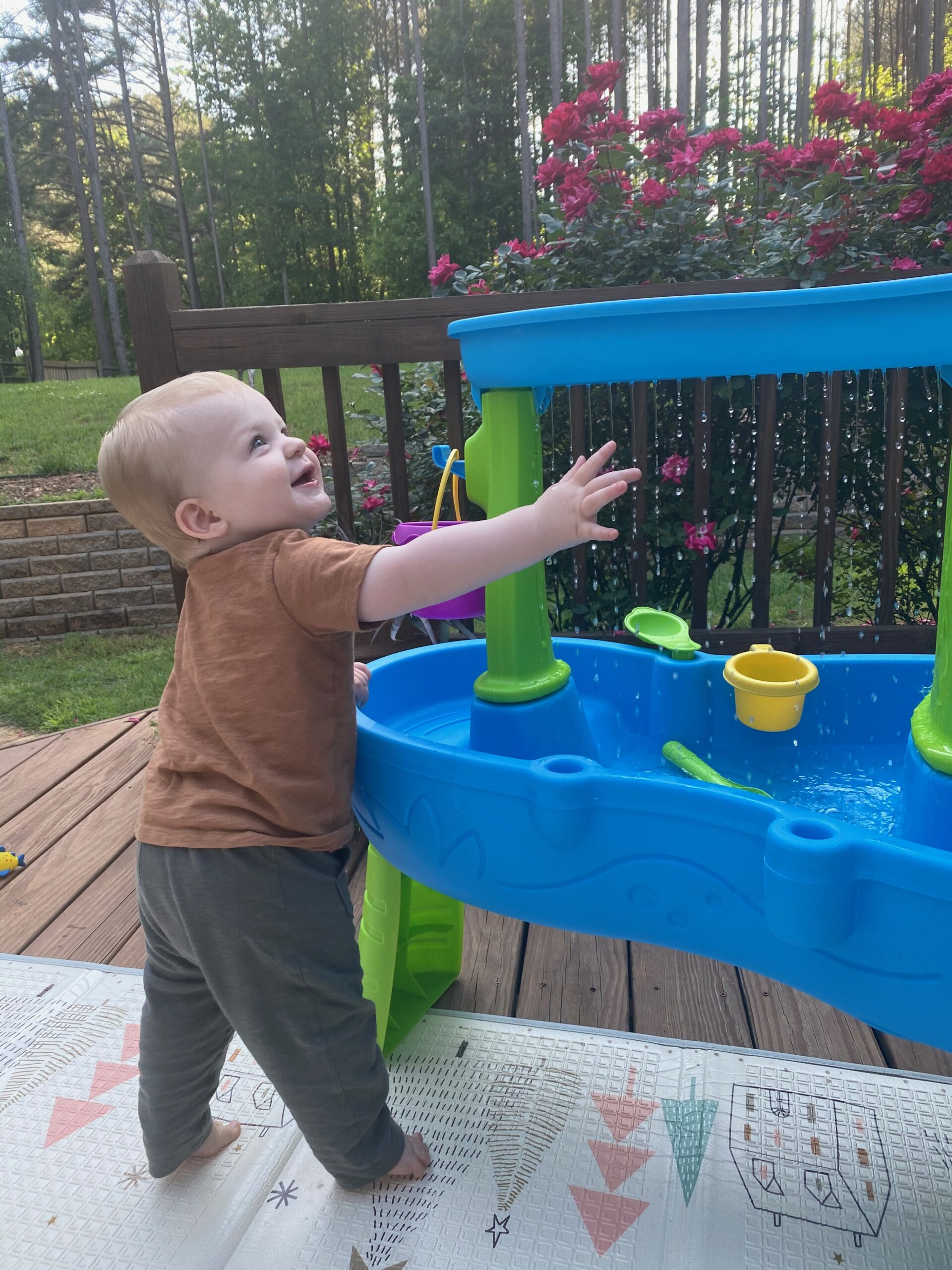 infant playing with water table