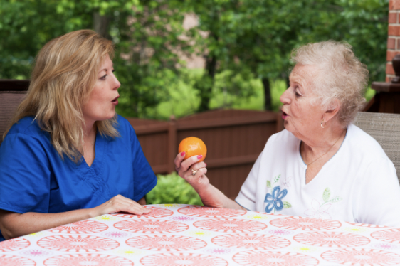 """A speech therapist and older woman are practicing the """"o"""" sound in orange"""