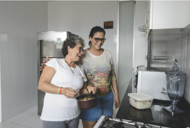 A woman and her therapist are working on motor skills via cooking