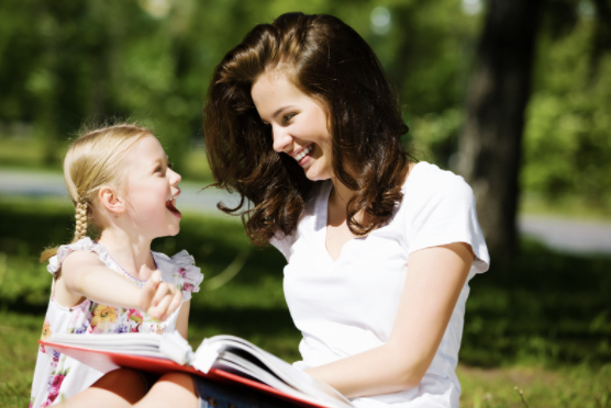 a girl and her mom are laughing at a book